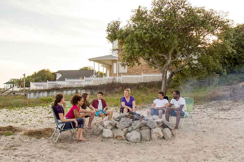 group seated around a fire on the beach